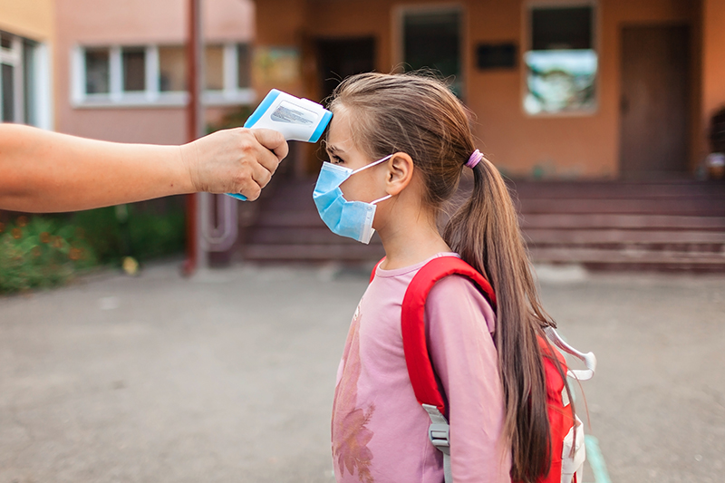 New normal back to school. A teacher measuring temperature to kid in medical mask with non-contact thermometer. Stay safe, new schooling guidance after coronavirus lockdown