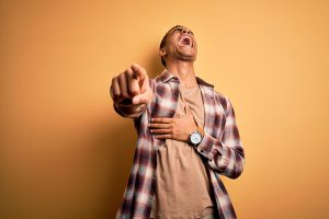 Young handsome african american man wearing casual shirt standing over yellow background laughing at you, pointing finger to the camera with hand over body, shame expression