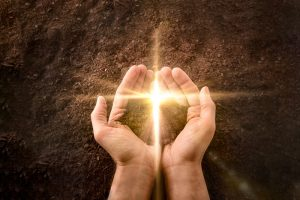 Hands together with a small mound of earth with a golden flash in the shape of a cross on a background of earth. Jesus resurrection concept. Horizontal composition. Top view.