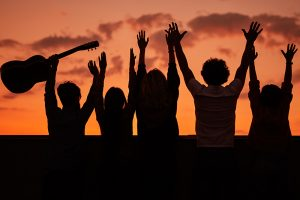Back view silhouettes of young people with guitar standing with raised arms against colorful sundown sky while having fun and enjoying summer party together